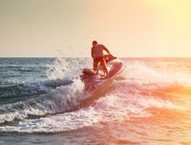 Silhouette of man on jetski at sea. Silhouette of strong man jumps on the jetski above the water at sunset royalty free stock image