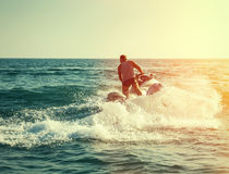 Silhouette of man on jetski at sea. Silhouette of strong man jumps on the jetski above the water at sunset stock image