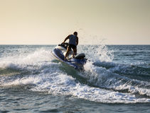 Silhouette of man on jetski at sea. Silhouette of strong man jumps on the jetski above the water at sunset stock photo