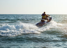 Silhouette of man on jetski at sea. Silhouette of strong man jumps on the jetski above the water at sunset stock photos