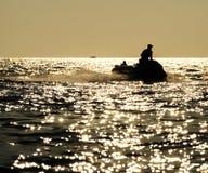 Silhouette of man on jetski at sea stock image