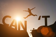 Silhouette man jump between can`t wording and can wording on mountain. Mindset for career growth business
