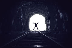 Silhouette of man jumping in abandoned railway tunnel