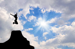 Silhouette of a man jumping with arms raised Royalty Free Stock Images