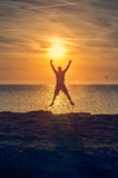 Silhouette of a man jumping on a beach during sunrise Royalty Free Stock Photo