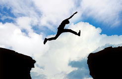 Silhouette of man jumping cliff. With cloudy sky Stock Photo