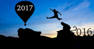 Silhouette man jumping. Between 2016 and 2017 hot air balloon wording Stock Photos