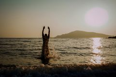 Silhouette of a man jumping out of the sea stock photo