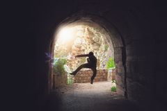 Fighter training in a dark tunnel. Silhouette of a man jumping while practicing karate in a dark tunnel stock photo