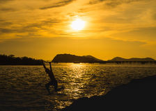 Silhouette man jumping in the sea Royalty Free Stock Image