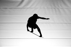 Silhouette of man jumping with skateboard deck Stock Photography
