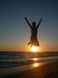 Silhouette of a man jumping in the sunset. Man jumping on the beach at sunset Royalty Free Stock Images