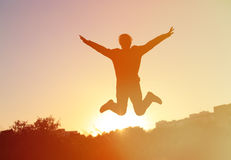 Silhouette of man jumping at sunset sky, happiness Royalty Free Stock Image