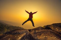 Silhouette man jumping into sunset sky Stock Images