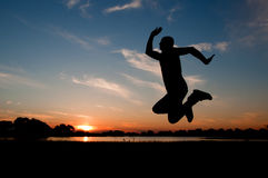 Silhouette of a man jumping in the sunset Royalty Free Stock Photo