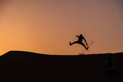 Silhouette of a man jumping. Man jumping on top of a Desert hill during sunset in dubai Royalty Free Stock Photos