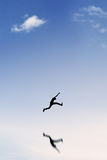 Silhouette of man jumping under blue sky Stock Photos
