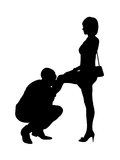 Silhouette of a man kissing a leg of a woman Stock Images