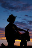 Silhouette of man kneel with saddle on knee. A silhouette of a teen cowboy kneeling with his saddle on his knee stock photography