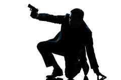 Silhouette man kneeling aiming gun Stock Photos