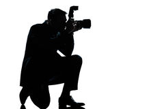 Silhouette man kneeling photographer Stock Photos