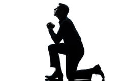 Silhouette man kneeling praying  full length Stock Photography