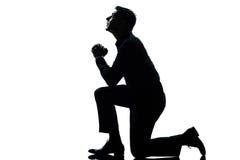 Silhouette man kneeling praying full length. One caucasian man kneeling praying full length silhouette in studio white background stock photography