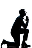 Silhouette man kneeling praying  full length Royalty Free Stock Image