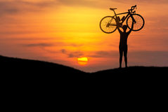 Silhouette the man lifting bicycle above his head on the meadow with sunset Stock Photography