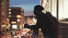 Silhouette of man looking to cityscape at night thinking and dreaming about future