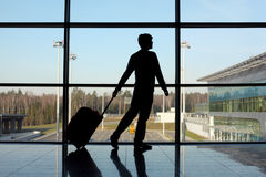 Silhouette of man with luggage near window Royalty Free Stock Image