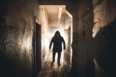 Silhouette of man maniac or killer or horror murderer with knife in hand in dark creepy and spooky corridor. Criminal robber. Or rapist concept in thriller stock image
