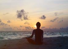 Silhouette of man meditating at sunset beach Stock Photos