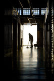 Silhouette of man moping floor. Silhouette of a man moping warehouse floor Royalty Free Stock Image