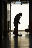 Silhouette of man moping floor. Silhouette of a man moping warehouse floor Royalty Free Stock Images