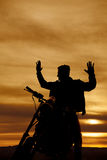 Silhouette of a man on a motorcycle hands up Royalty Free Stock Photos