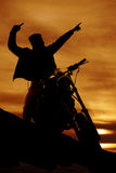 Silhouette of a man on a motorcycle pointing. A silhouette of a man on a motorcycle pointing Stock Images