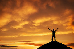 Silhouette of a man on a mountain top against the sunset sky. royalty free stock photos