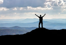 Silhouette of a man on a mountain top. stock photo