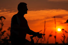 Silhouette of a man on muontain-bike Stock Photo