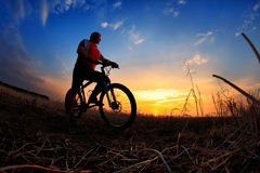 Silhouette of a man on muontain-bike Stock Photos