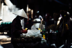 Silhouette of a man in the national Asian hat. Street vendor wit Royalty Free Stock Photography