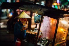 Silhouette of a man in the national Asian hat. Street vendor wit Stock Photography
