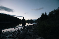 Silhouette of Man Near Body of Water Near Silhouette of Trees and Mountains Stock Photography