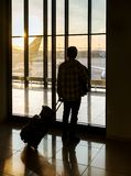 Silhouette of man near window in airport stock photo