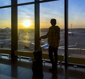 Silhouette of man near window in airport stock images