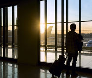 Silhouette of man near window in airport stock photography