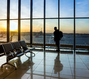 Silhouette of man near window in airport Stock Photos