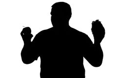Silhouette of a man with obesity choosing between an apple and a Stock Photos