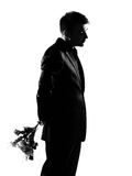 Silhouette  man offering flowers. Silhouette caucasian business man offering flowers expressing behavior full length on studio isolated white background Royalty Free Stock Photo